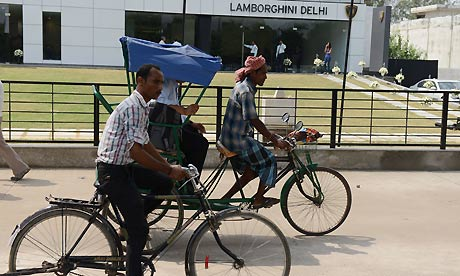 A bike and a rickshaw pass Lamborghini's New Delhi showroom